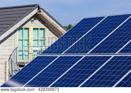 Solar Panels On The Field In The Countryside With House On Background. Solar Power Plant. Blue Solar