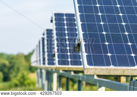 Solar Panels In An Agriculture Green Field In The Countryside. Solar Power Plant. Blue Solar Panels.