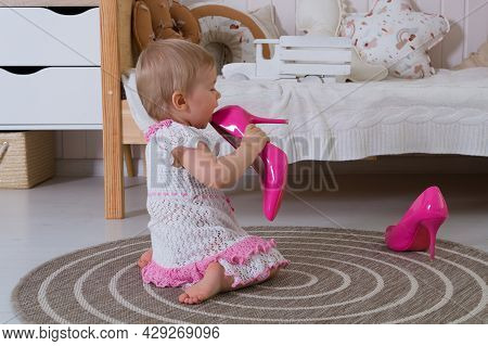 A One-year-old Girl In A White And Pink Openwork Dress Licks Her Mother's Women's Hot Pink High-heel