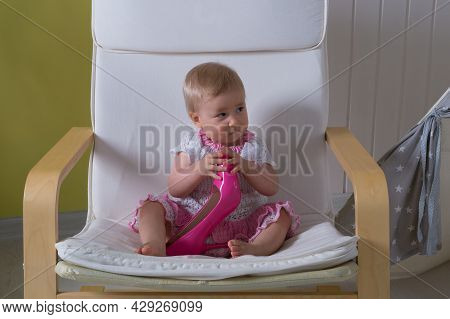 A Little One-year-old Girl In A White-pink Knitted Dress Sits On A White Armchair And Holds An Adult