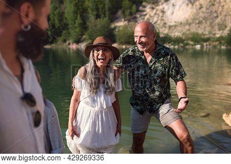 Happy Multigeneration Family On Summer Holiday, Having Fun By Lake.
