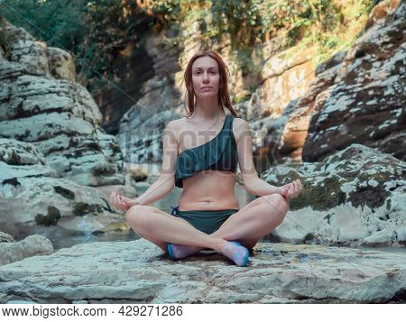 The Girl Sits Cross-legged On A Stone By The River, Surrounded By Rocks. Meditation In Nature. Yoga