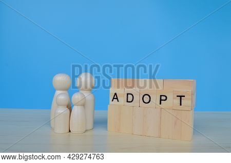 Wooden Doll Figures Standing On Wooden Blocks With Text Adopt