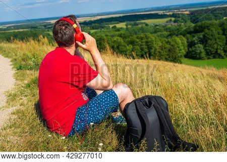 Young Male Person Enjoys Music In Headset From Cell Phone In Mountains.beautiful Scenery Male Listen