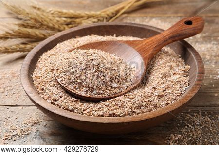Wheat Bran And Spoon In Bowl On Wooden Table