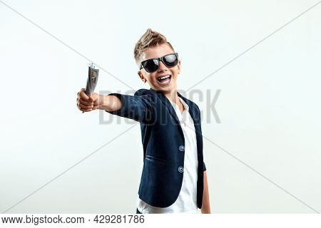 A Rich Boy In Glasses Holds Dollars Against The Background Of Falling Banknotes. Knows How To Make M