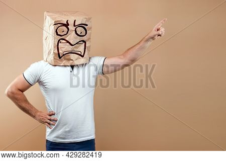 Men Put A Paper Bag On Their Heads With A Drawn Screaming Face, Points A Finger At You Isolate On A