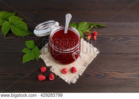 Raspberry Jam In A Glass Jar On A Linen Napkin On A Dark Wooden Background. Conservation And Summer