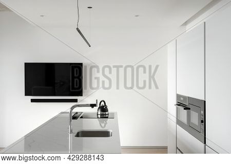View Of White Modern Kitchen With Black Tv Hanging On White Empty Wall, Counter With Faucet And Sink