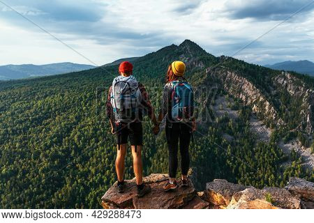 A Man And A Woman In Tourist Equipment Are Standing On A Rock And Admiring The Panoramic View. A Cou