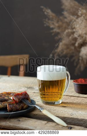 Glass With Beer And Foam And Fork With A Piece Of Sausage And Ketchup On A Wooden Background, German