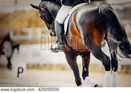 Equestrian Sport. The Legs Of The Rider In The Stirrup, Riding On A Horse. The Black Fluttering Tail