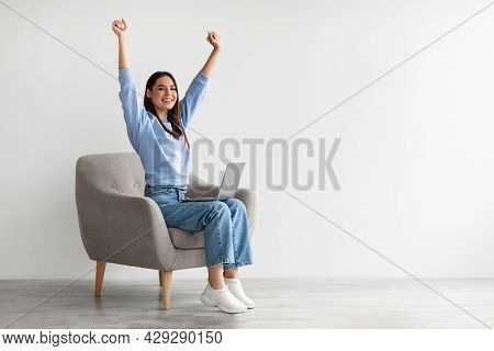 Ecstatic Woman Sitting In Armchair With Laptop, Lifting Hands Up, Making Yes Gesture, Celebrating On