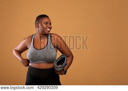 Chubby Black Woman Holding Yoga Mat Looking Aside