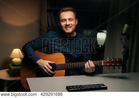 Medium Shot Of Cheerful Guitarist Singer Man Emotionally Singing Into Condenser Microphone And Playi