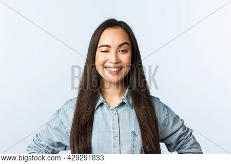 Lifestyle, People Emotions And Beauty Concept. Self-assured Cheerful Female Freelancer Wink And Smil