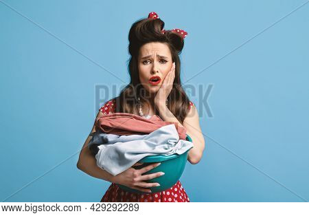 Exhausted Young Pinup Woman Holding Laundry For Washing Or Ironing On Blue Studio Background