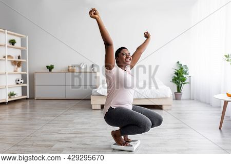 Successful Weigt Loss. Overjoyed Plump Black Woman Sitting On Scales, Raising Hands Up, Achieving Sl