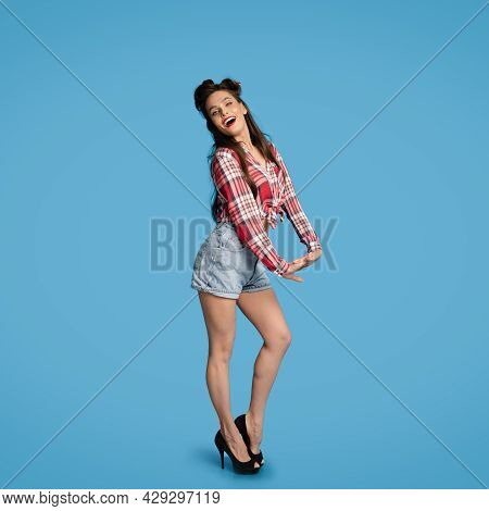 Flirty Young Pinup Woman In Retro Shirt And Shorts Posing, Smiling At Camera On Blue Studio Backgrou