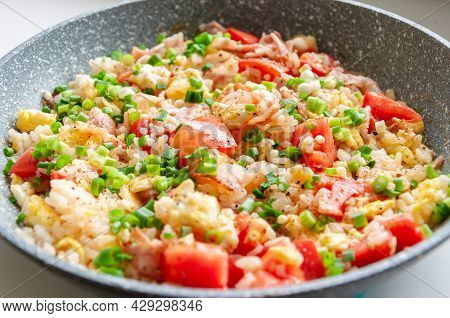 Stir Fried Rice On Pan. Tasty Rice Cooked With Vegetables And Bacon Close-up In A Pan On The Table.