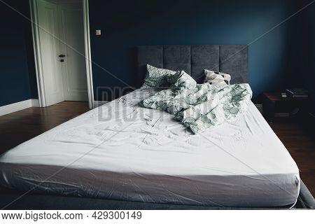 Dark Blue Color Bedroom Interior Design. Unmade Bed In The Room. Minimalism, Interior, Comfort And B