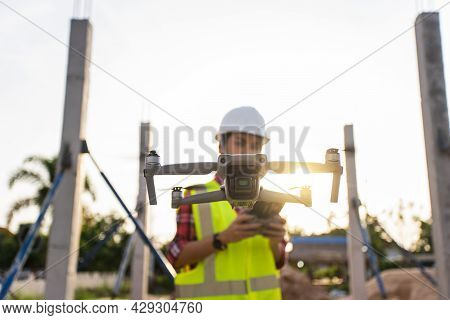 Selective Focus Drone. Asian Woman Engineer Surveyor Control Drone For Aerial View Structure Inspect