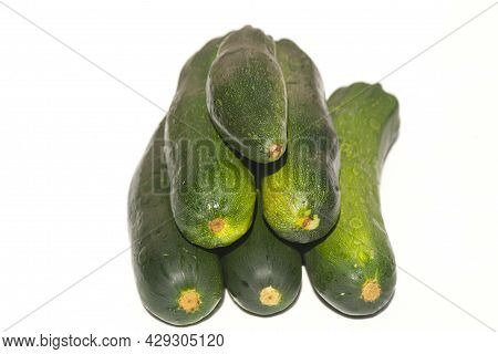Zucchini Lie On A White Surface. Zucchini Are Stacked In A Heap On A White Surface