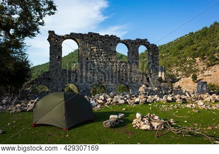 Camping next to Alakilise ruins along Lycian way hiking trail, Green tent stands near wall remains of Alakilise or Church of the Angel Gabriel in Lycia, near Finike and Demre, Antalya Province, Turkey