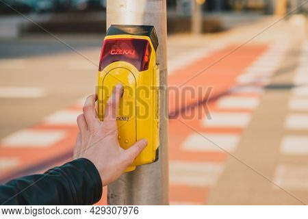 Man Pushing The Yellow Button At A Traffic Light For Pedestrians On The Background Of The Road. Czek