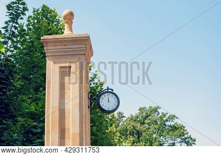 Street Clock On A Pole Against Blue Sky And Green Foliage With Copy Space. Vintage Clock Measuring T