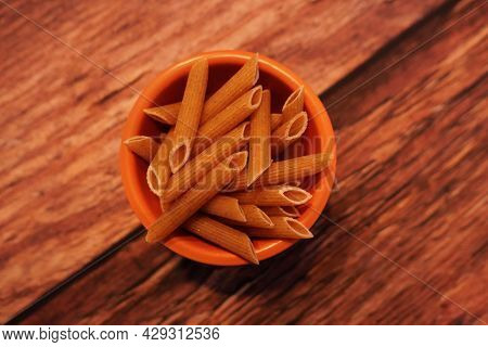 Small Terracotta Pot Of Uncooked Wholemeal Penne Pasta On Wooden Background