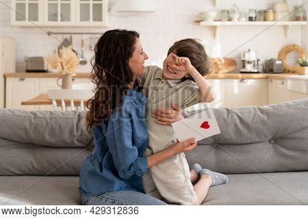 Family Celebration: Small Kid Presenting Mom Greeting Card With Heart On Mother Day, Birthday Or Val