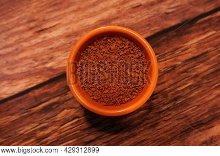 Little Terracotta Dish Of Brown Instant Coffee Granules On Wooden Background