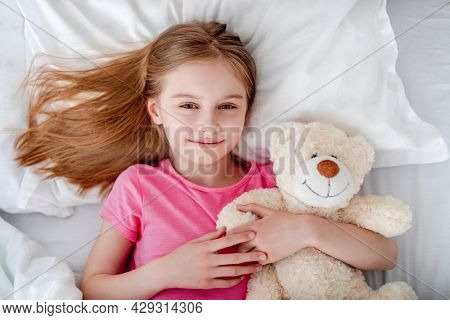 Little beautiful girl lying in the bed hugging teddy bear and smiling. Preteen child resting wearing pink t-shirt and holding toy. Portrait of pretty female kid