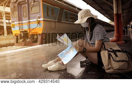 Young Female Tourists Or Passengers Wearing Protective Face Mask Sit And Look At The Tourist Map On