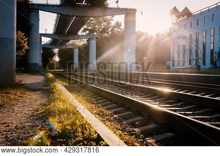 Railway Station On Sunset. Tram Station. Lines Of Train Rails. Perspective View. The Passenger Is Wa