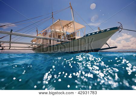 Filipino outrigger with diving tanks waiting for divers to come aboard and ready to navigate poster