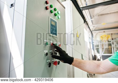 Man Worker Press Button Equipment Of The Switchboard. Strip The Cable Channels For The Wires.