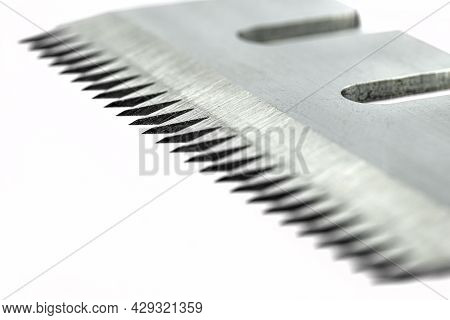 A Macro Photo Of A Serrated Industrial Blade For Tape Cutters, Isolated On A White Background.
