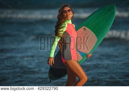 Beautiful young woman surfer. Girl with surfboards on a beach