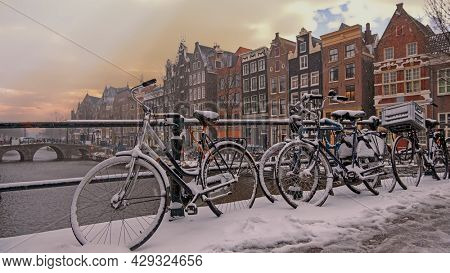 City scenic from a snowy Amsterdam  with a cloudy sunrise in winter in the Netherlands