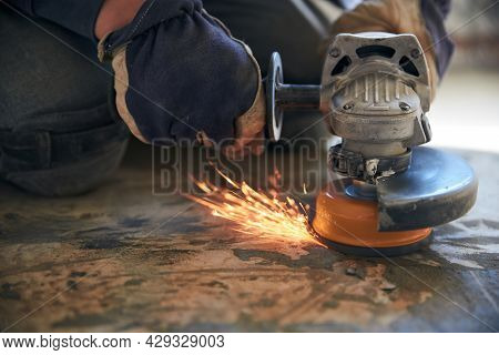 A Man In Gloves And Protective Knee Pads On The Legs Grinds The Floor With A Grinder