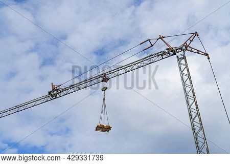 A Wooden Euro Pallet Lifted By A Tower Crane Against A Blue Sky With Light Clouds.