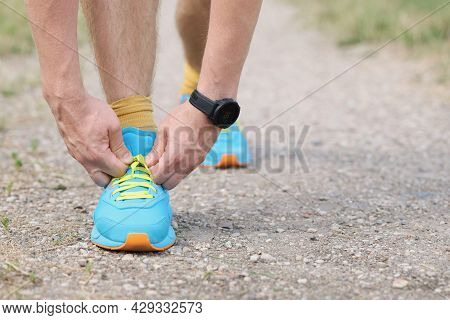 Man Runner Ties Shoelaces On The Ground With Hands