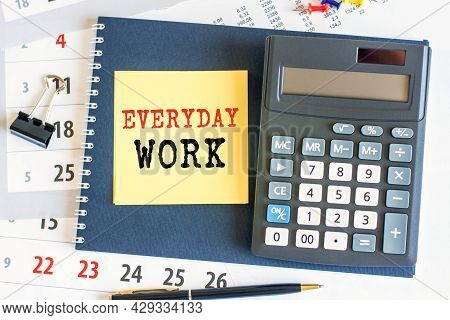 A Yellow Piece Of Paper With The Text Everyday Work And The Calculator Are Lying On The Notepad. The