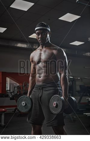African American Sports Guy Bodybuilder With Naked Muscular Torso Exercising With Dumbbells In Gym