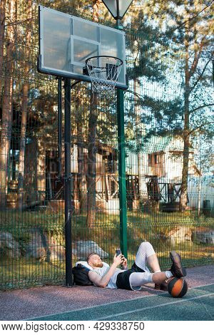 Male Basketball Player Using Phone Sportive App Relaxing After Workout Outdoors Under Basketball Hoo