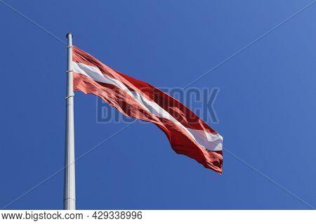 Latvian National Flag On A Background Of Blue Sky.