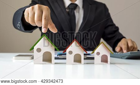 Real Estate Agents Offer Energy-saving Green Roof Home Models, Home Loan Concepts. Finance And Mortg