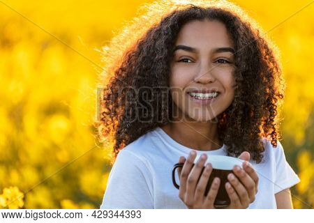 Beautiful happy mixed race African American girl teenager female young woman smiling drinking coffee or tea outdoors in a field of yellow flowers